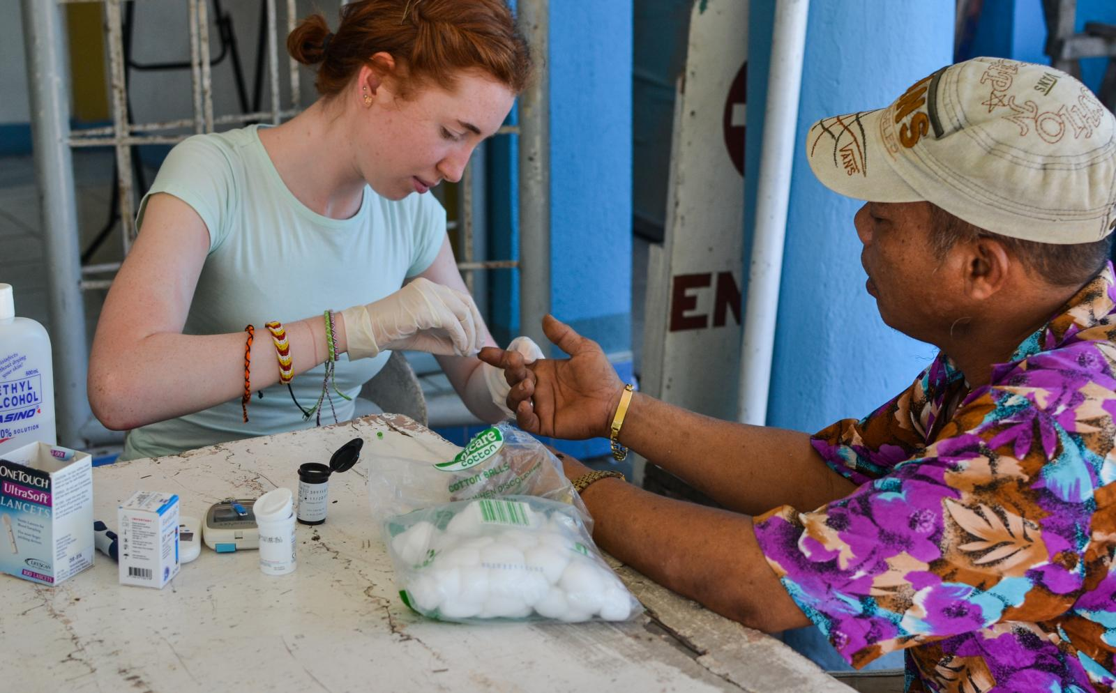A medical volunteer assists a man during a medical outreach in Philippines